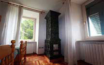 Stufa verde scuro verticale in ambiente classico con pavimento in legno