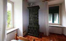 Stufa verde scuro verticale in ambiente classico con pavimento in legno 2