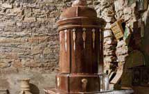 Stufa antica di colore marrone presso il laboratorio di StufArte