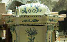 Stufa antica di colore bianco decorata a mano presso i laboratori di StufArte