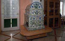 Stufa decorata a mano con disegni floreali di colore verde ed azzurro con panca