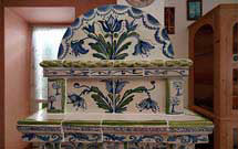 Dettaglio di stufa decorata a mano con disegni floreali di colore verde ed azzurro con panca