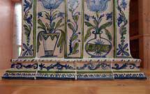 Dettaglio parte bassa di stufa decorata a mano con disegni floreali di colore verde ed azzurro con panca