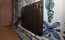 Portello di caricamneto di una stufa decorata a mano con disegni floreali di colore verde ed azzurro con panca