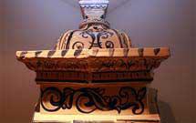 Dettaglio superiore di una stufa a olle bianca con decorazione di colore blu